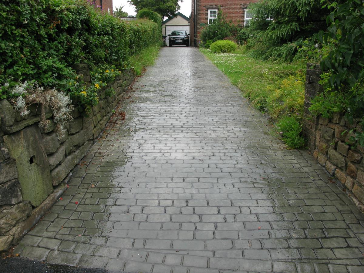Mews cobblestone effect textured concrete coloured in green stone and with a gloss finish, installed to a long sloped driveway in Preston.