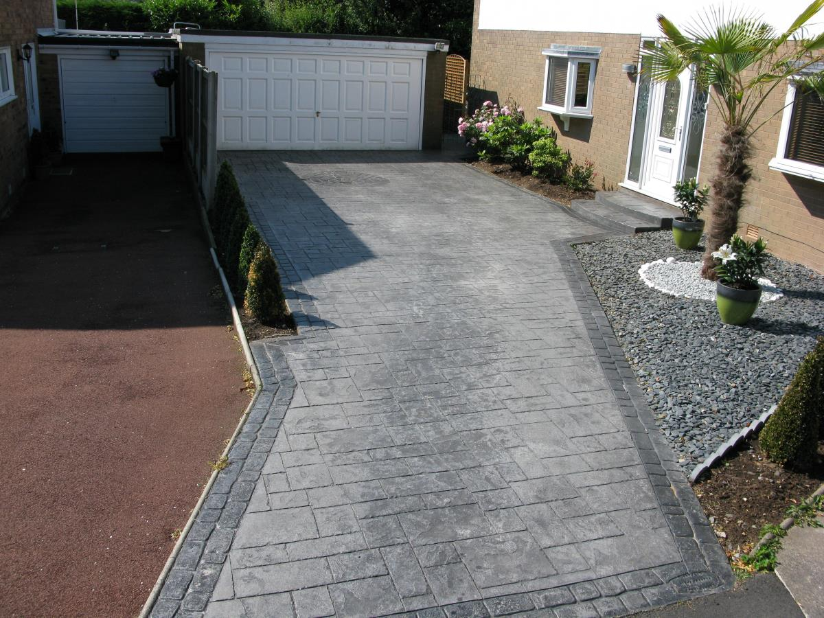 Pattern imprinted driveway in Blackpool in basalt grey ashlar slate, with stone grey cobble edges.
