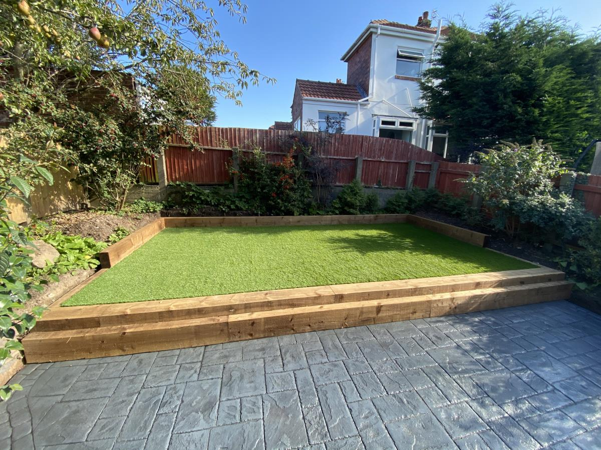 Artificial grass lawn area boxed in by sleepers as a step off from a levelled off patio for a Blackpool garden.