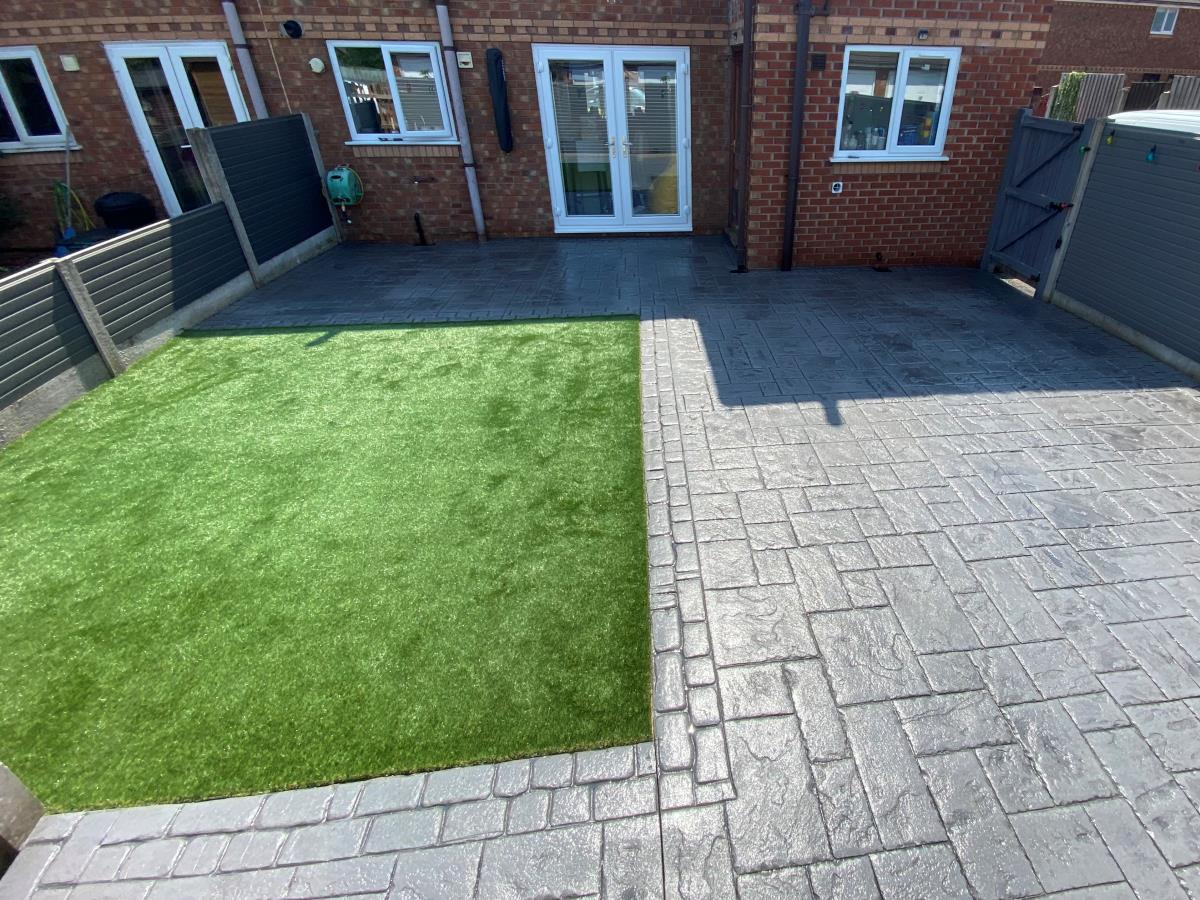 Artificial grass lawn and stamped concrete patio laid to a Garstang back garden, offering a great entertaining space.