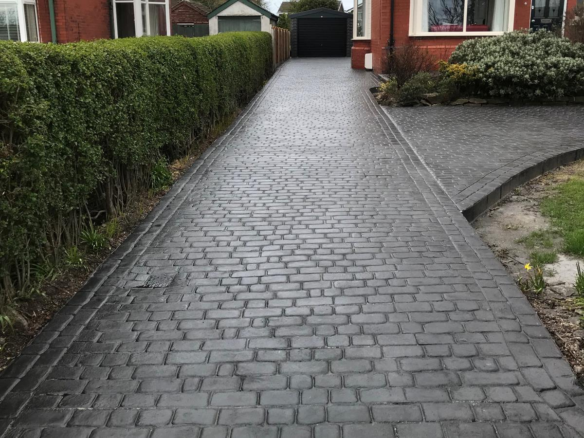 Long charcoal black stamped concrete driveway installed in Carleton, near Poulton, in cobble pattern with double cobble border.
