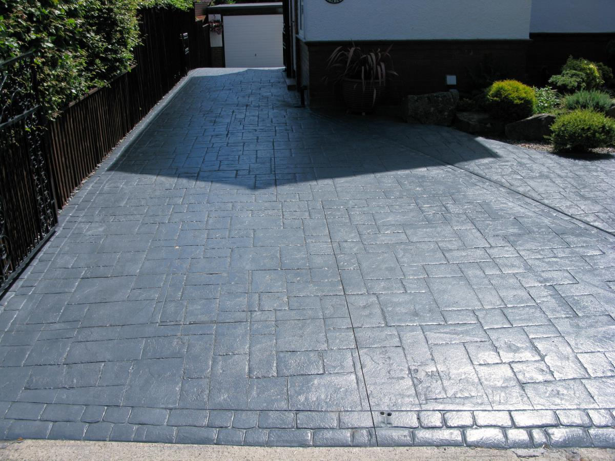 Large pattern imprinted driveway in ashlar slate with mews cobblestone edging for a Cleveleys home, featuring a slope down to the garage.