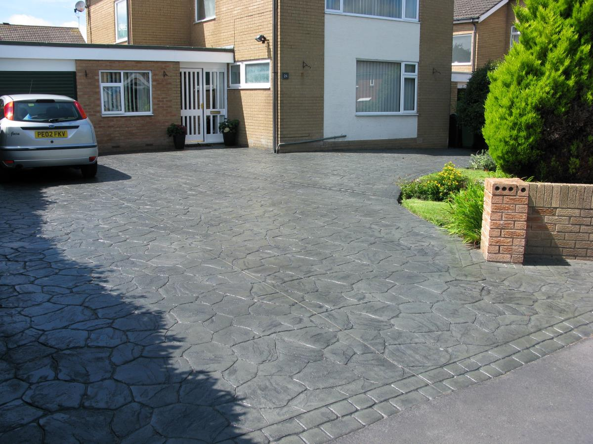 Crazy paving style pattern imprinted concrete driveway with mews cobblestone edging in the Knott End area.