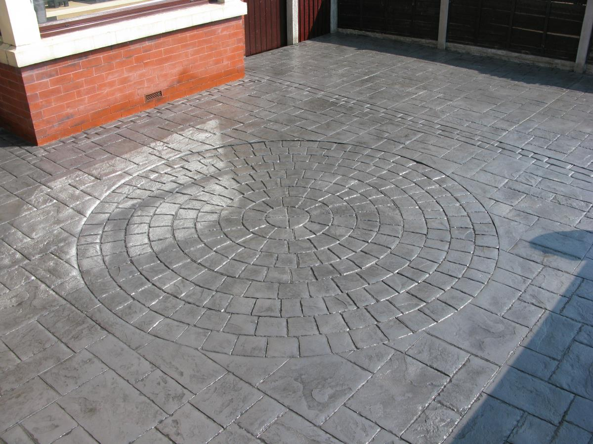 An ashlar slate coloured basalt grey imprinted concrete driveway with large circle inset for a Leyland home.