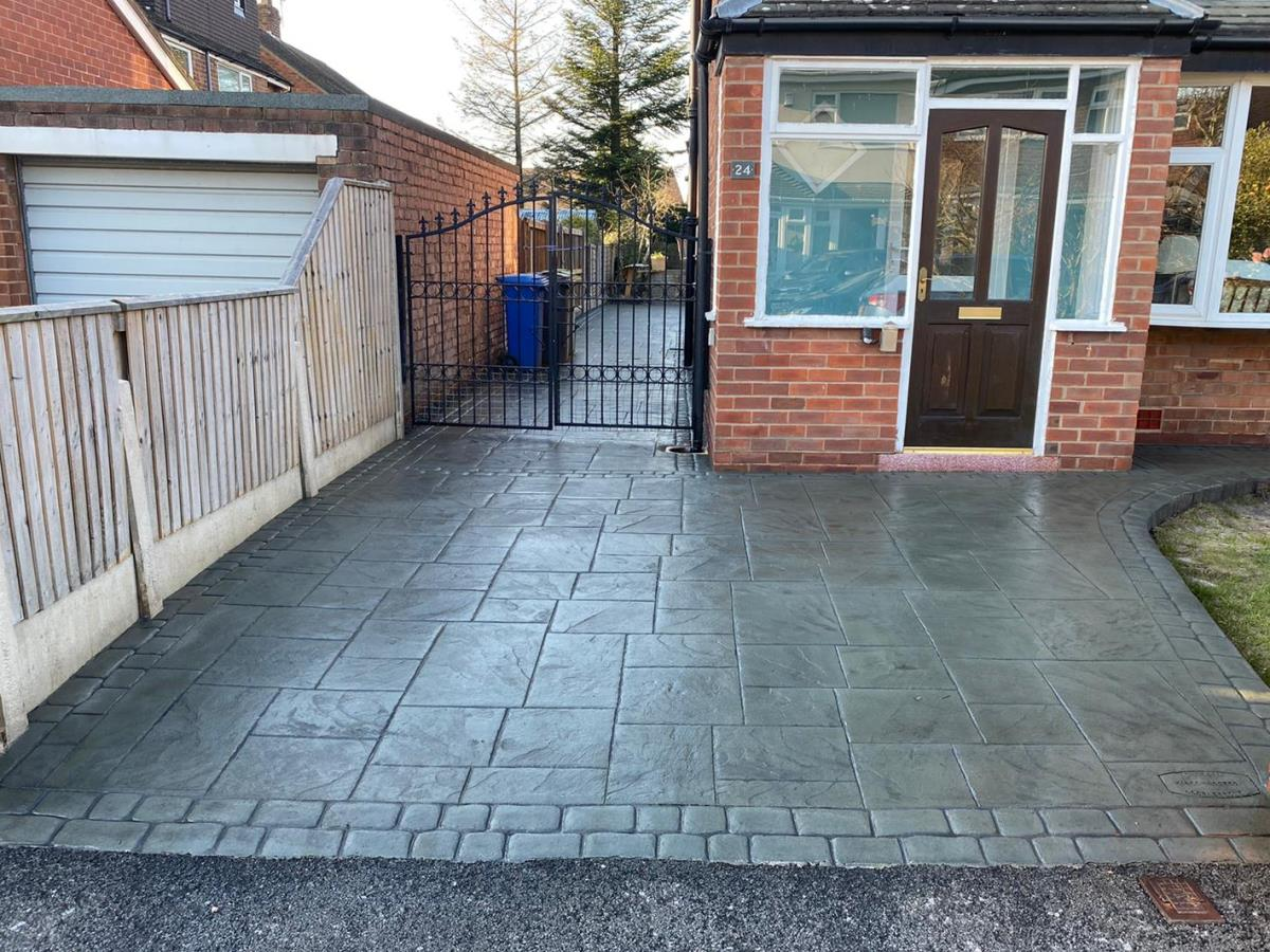Pattern imprinted concrete driveway in grand ashlar style in slate green grey with cobble border for a Poulton customer.