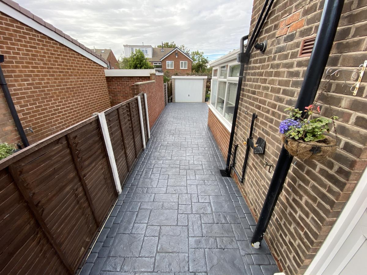 Stamped concrete driveway in French grey, ashlar slate style installed to the side of a Poulton home.!!Images/Photo_Pattern_Imprinted_Concrete_Garden_Path_Thornton_Cleveleys.jpg
