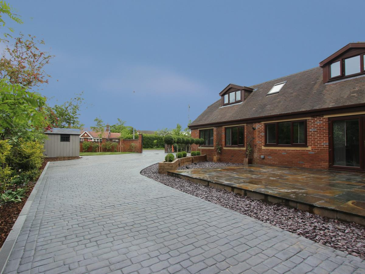Large wrap-around stamped concrete driveway and landscaping for Highpoint at Singleton, Poulton.