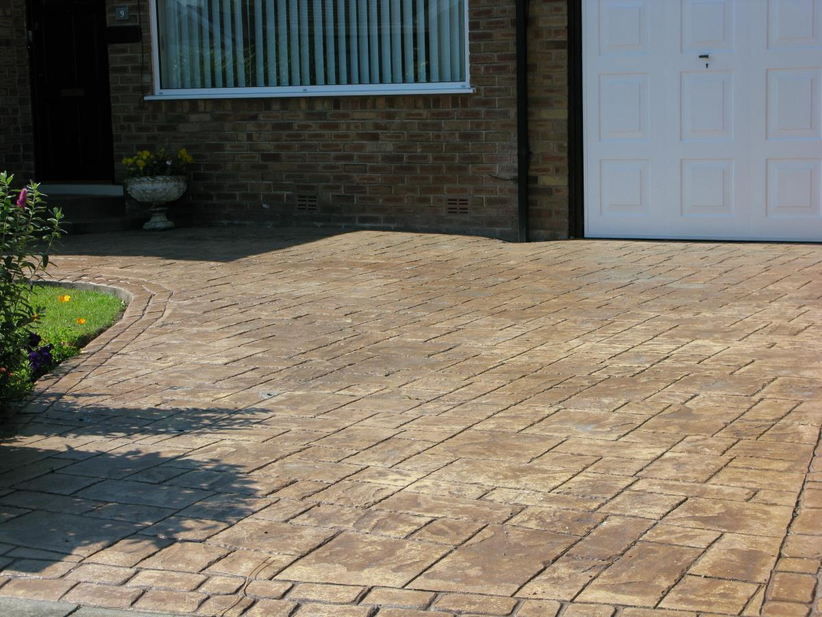 Stamped concrete driveway in ashlar slate style finished in country sandstone effect for a Kirkham home.