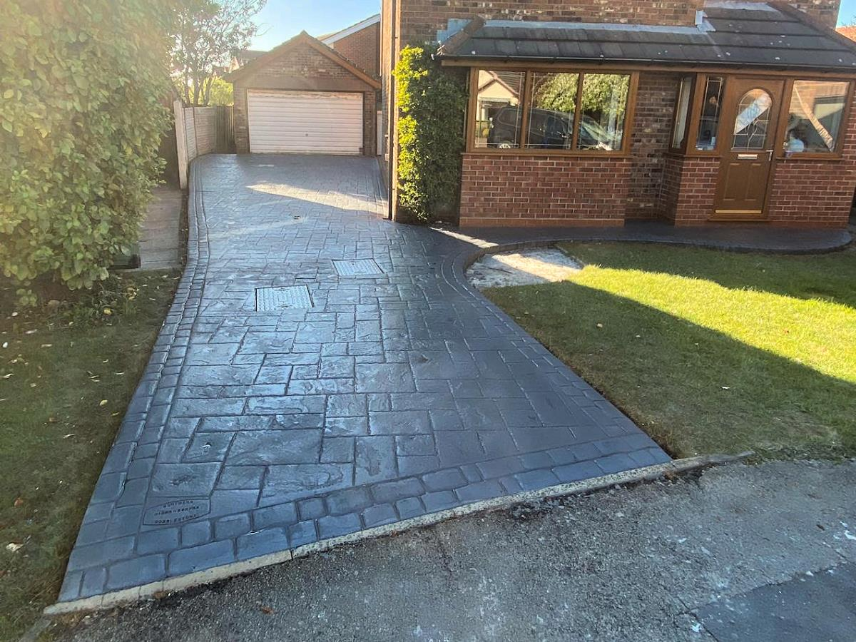Stamped concrete driveway and path to front door in french grey ashlar slate style at Over Wyre home.