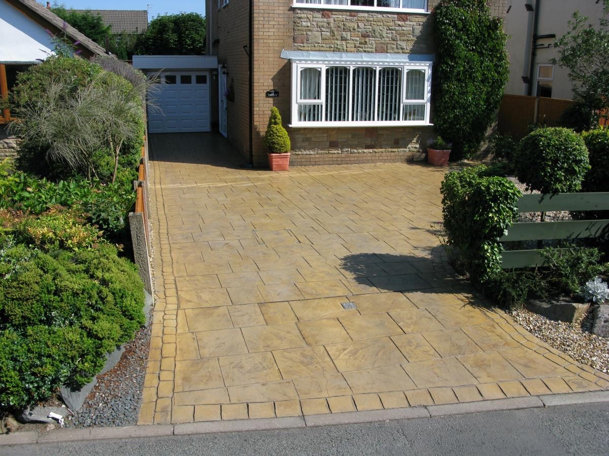 Pattern imprinted concrete driveway finished in golden beige walkway slate style for a Fleetwood customer.