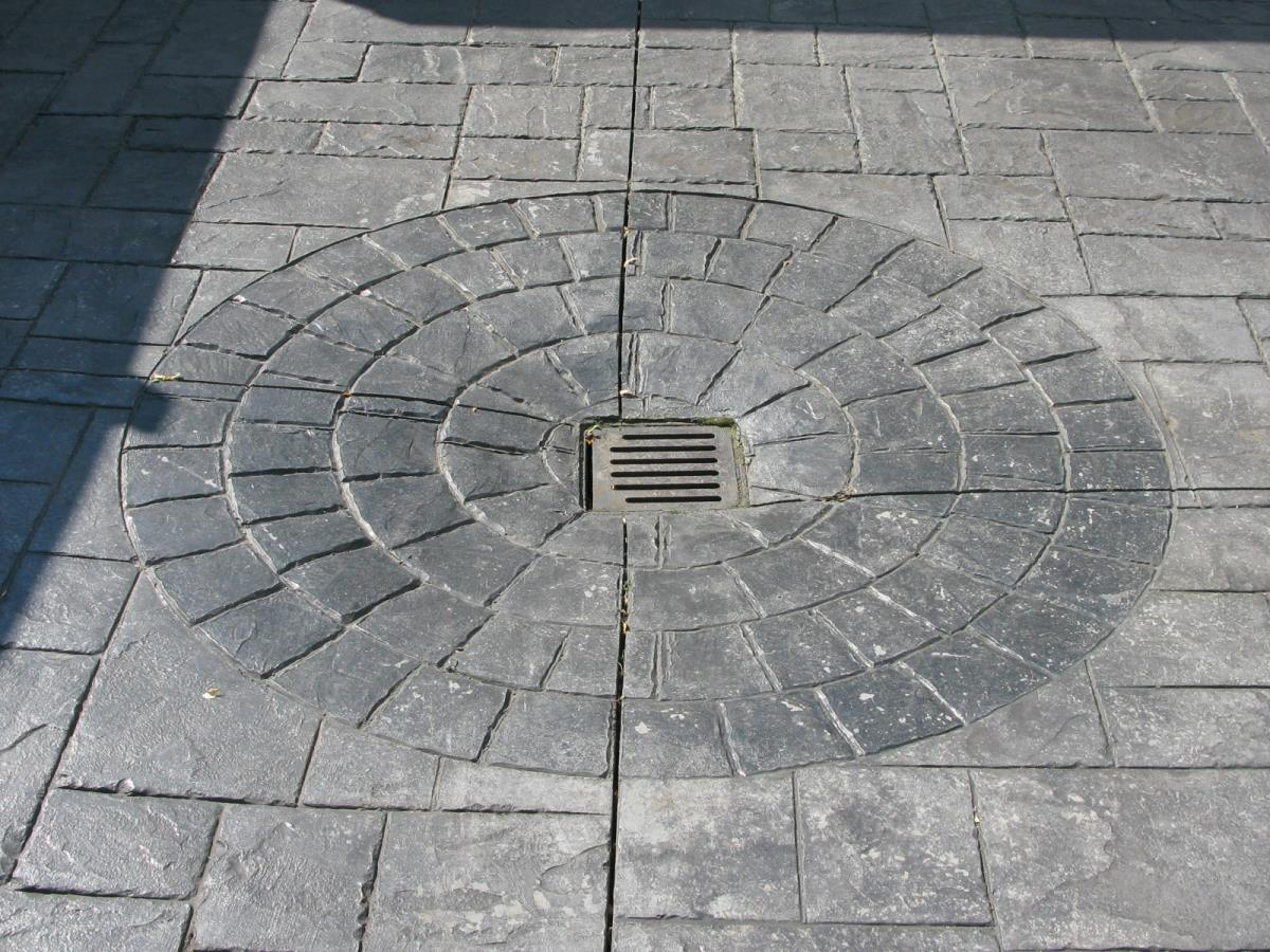 Example of incorporating drainage into a circle inset using stone grey cobble edges at a household in Poulton-le-Fylde, Lancashire.