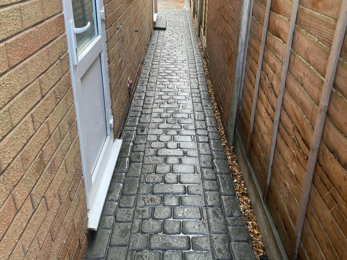 Mews cobblestone styled stamped concrete pathway installed to the side of a Poulton-le-Fylde property.
