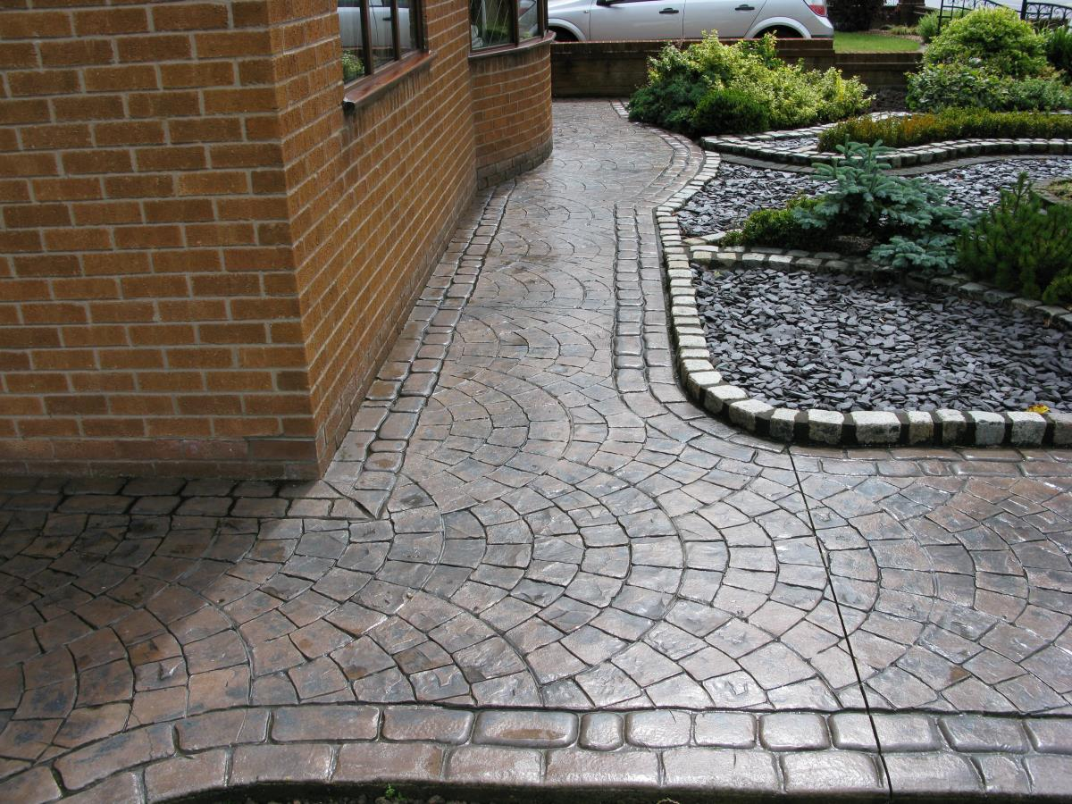Toffee coloured concrete garden path textured with European fan and edged with mews cobblestone laid at a home in Leyland.