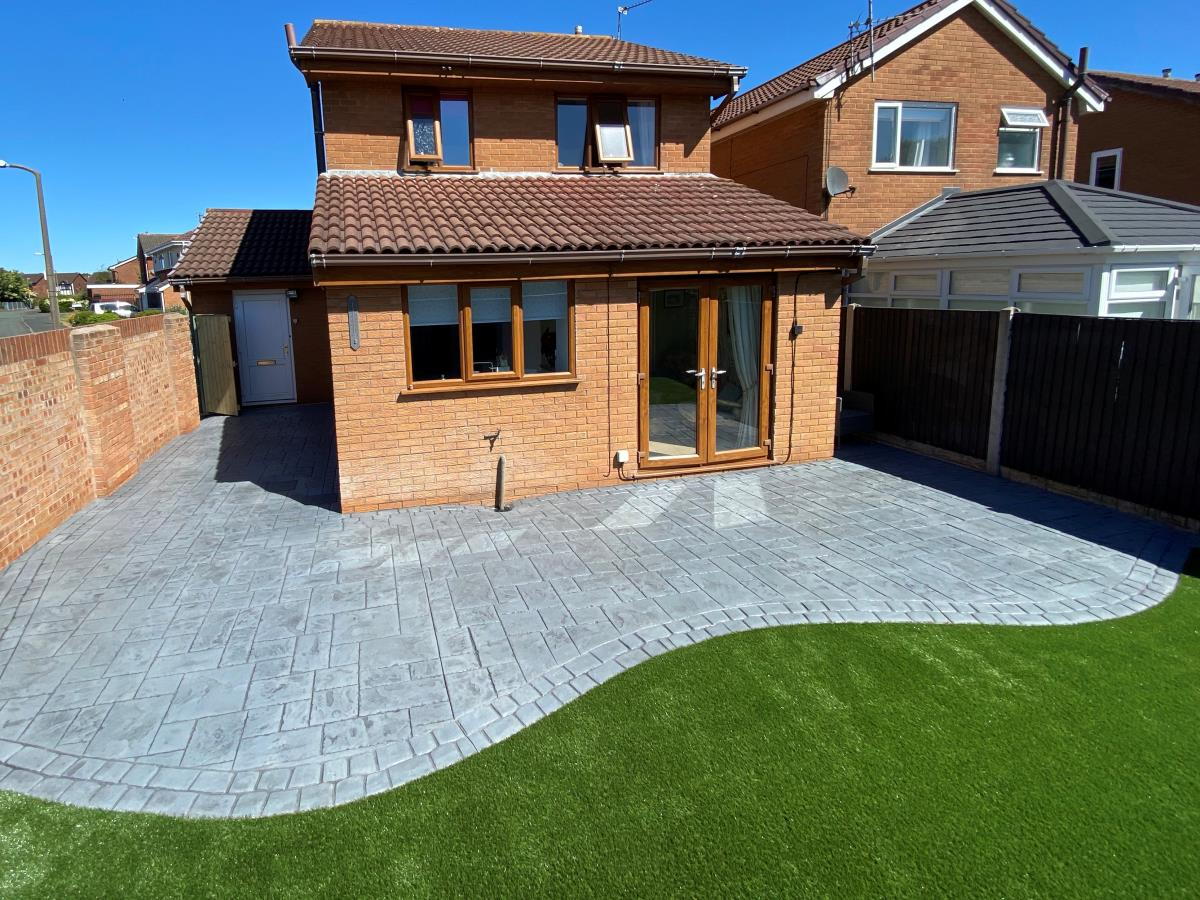 Platinum silver colour imprinted concrete patio and artificial grass installed to a property in the Cleveleys area.