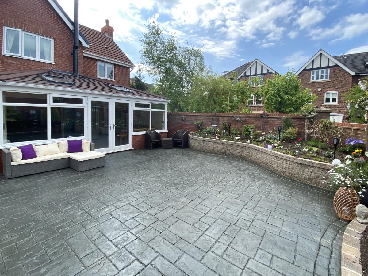Large ashlar slate pattern decorative concrete patio with additional brickwork to create rustic flower beds for Poulton-le-Fylde garden.