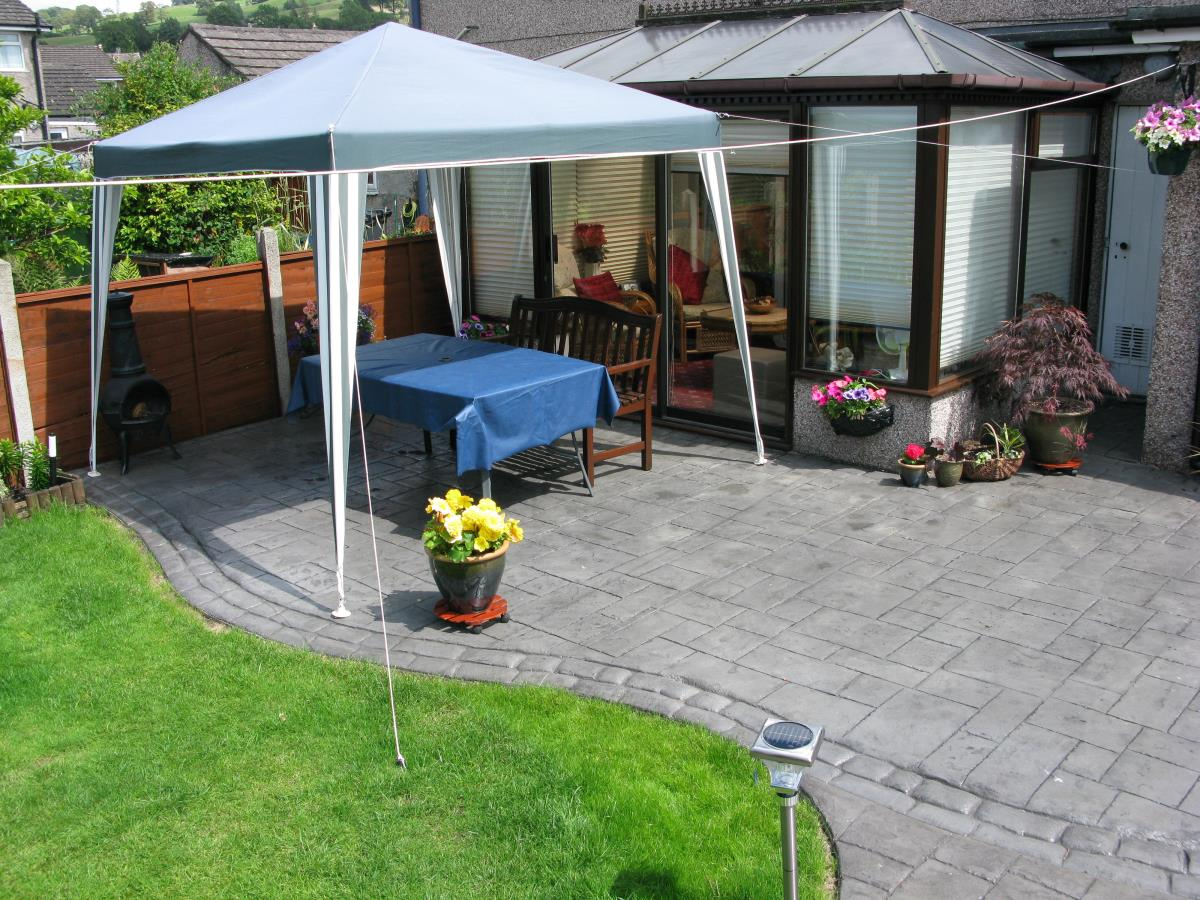 Concrete patio with satin finish stamped with ashlar slate and mews cobble edging in Leyland.
