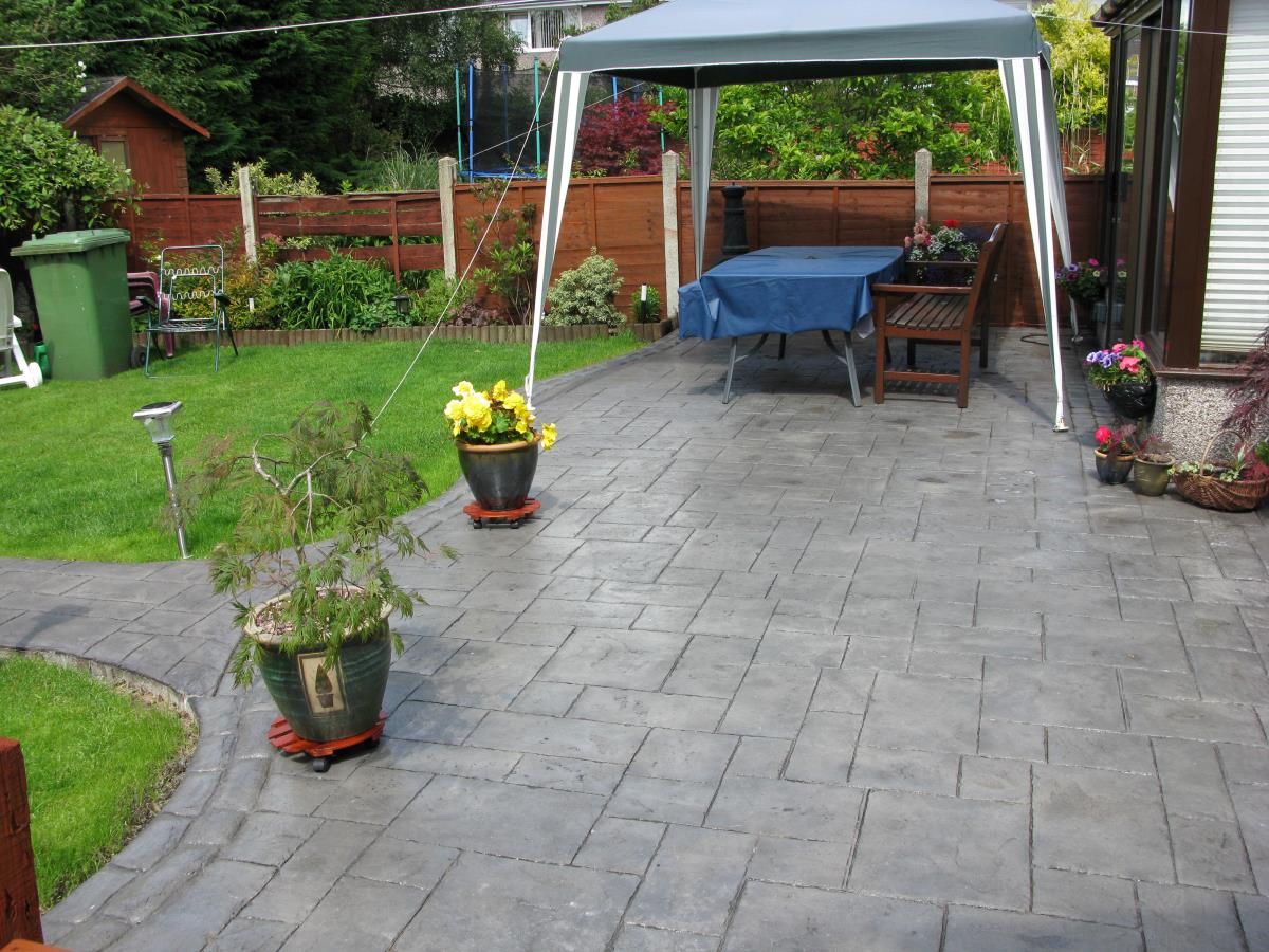 Stamped concrete patio with satin finish in ashlar slate style and mews cobble edging in Kirkham.