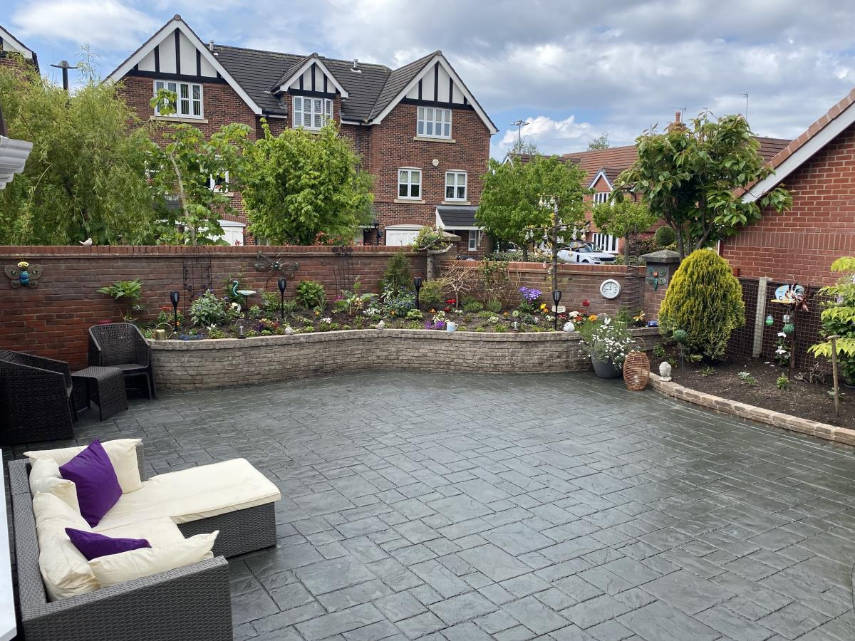 Large ashlar slate decorative concrete patio with additional brickwork creating flower beds in Poulton-le-Fylde.