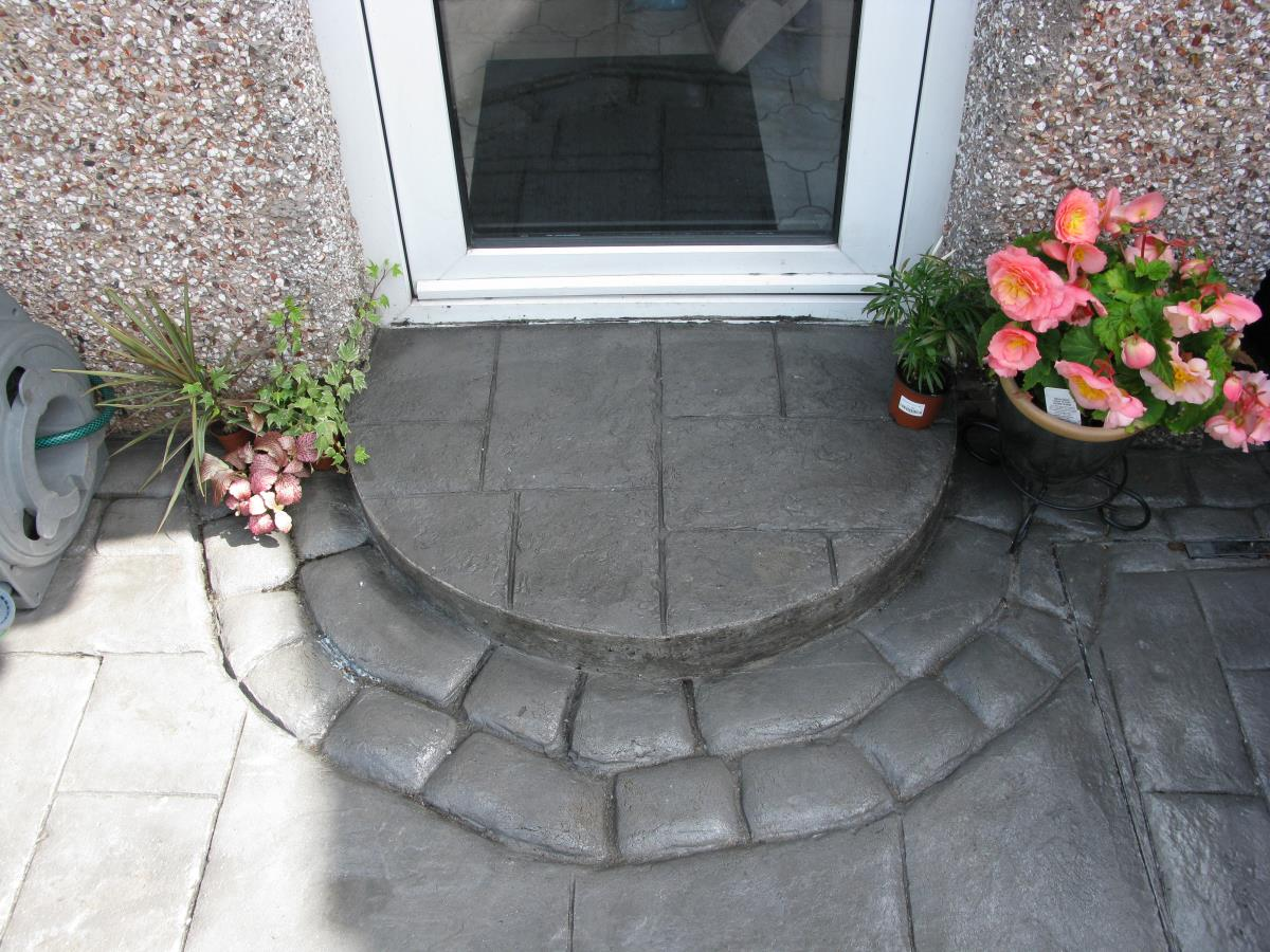 Semi circular silver grey coloured concrete step in ashlar slate style edged with mews cobble for Preston rear garden.
