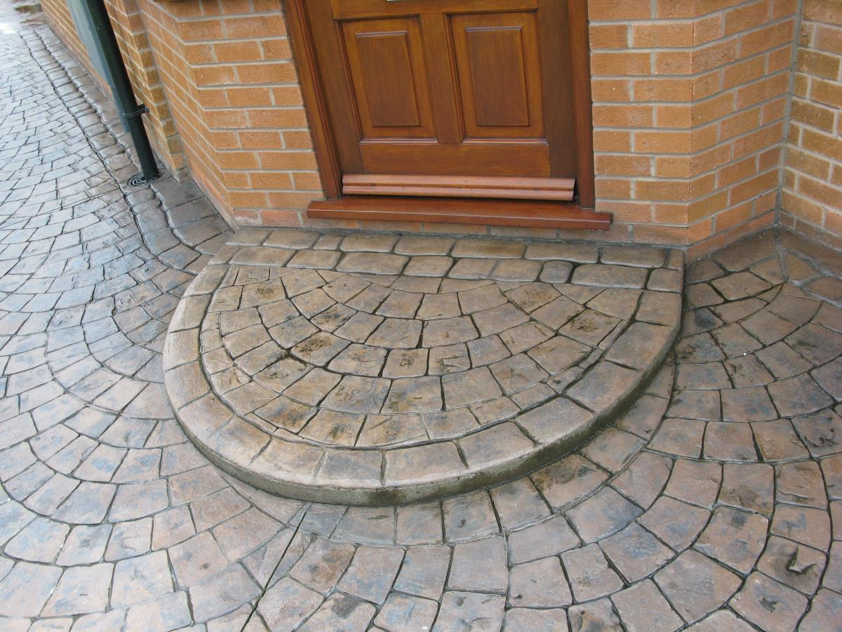 Semi circular European fan style concrete step edged with mews cobblestone, coloured in toffee with a satin finish for home in Poulton-le-Fylde.