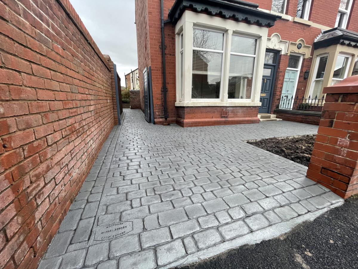 Installation of a driveway and pathways to a Poulton home in platinum silver coloured stamped concrete in mews cobble style.