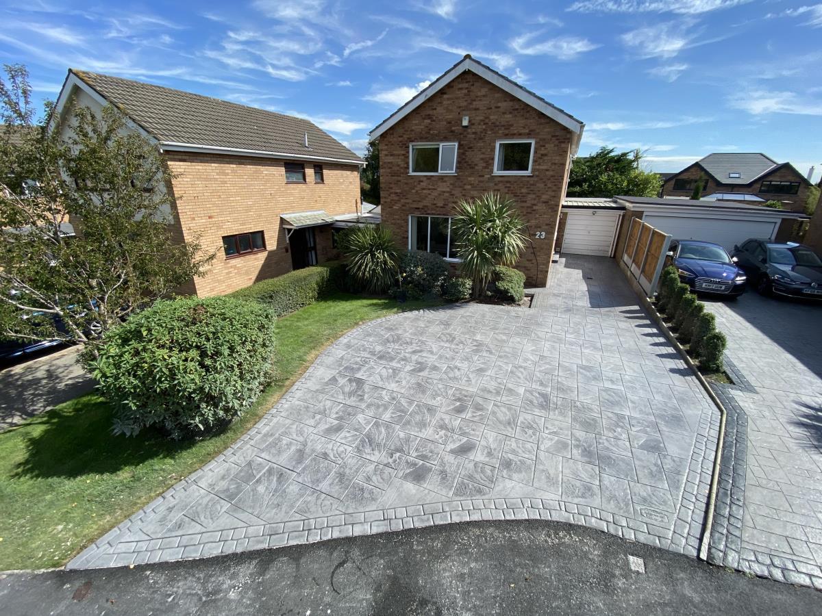 Stamped concrete driveway for a Poulton home in a dove grey, grand ashlar slate style with a double cobble border.