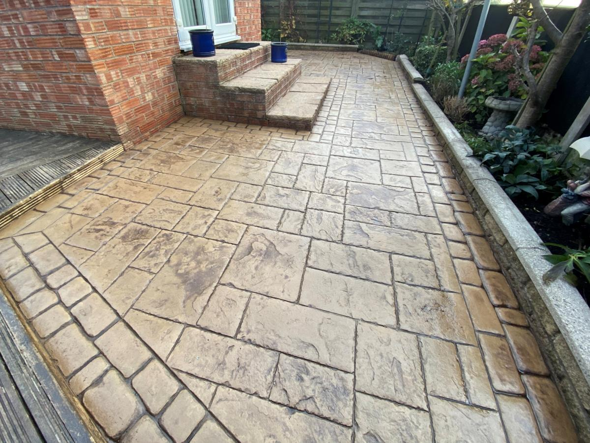Stamped concrete patio installed to a property in Poulton in Arizona tan coloured ashlar slate style and cobble border.